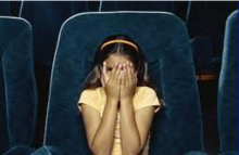 Girl covering her eyes in movie theater seat